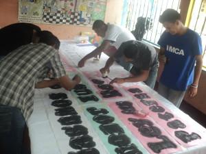 Colaboradores elaborando manta sobre ley 623
